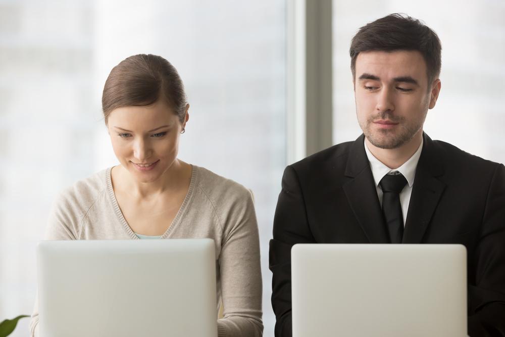隣の人のパソコンを覗き見する男性